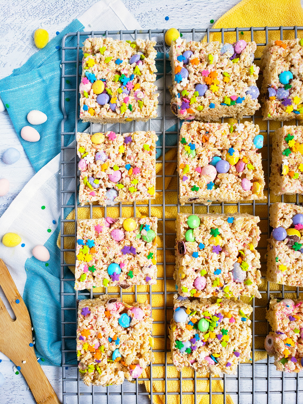 The Best Easter Rice Krispies Treats made with M&Ms, Cadbury eggs, and sprinkles. Cut into squares on a wire rack. The perfect Spring treat