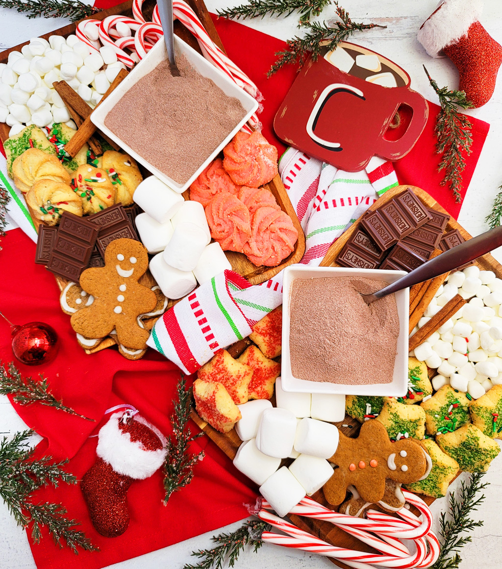 DIY Holiday Hot Cocoa Charcuterie Board on a wooden cutting board with gingerbread cookies, marshmallows, and hot chocolate mix. The perfect Christmas charcuterie board. www.littleeatsandthings.com