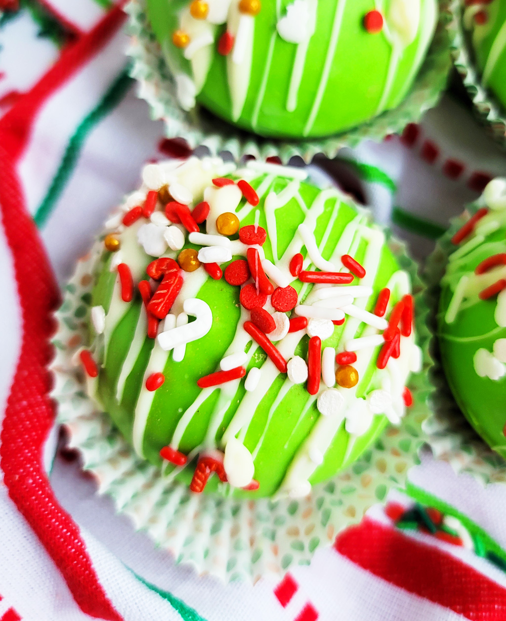 Green Grinch hot chocolate bombs with white chocolate drizzled on top, with Christmas sprinkles. DIY Hot chocolate bomb recipe. www.littleeatsandthings.com