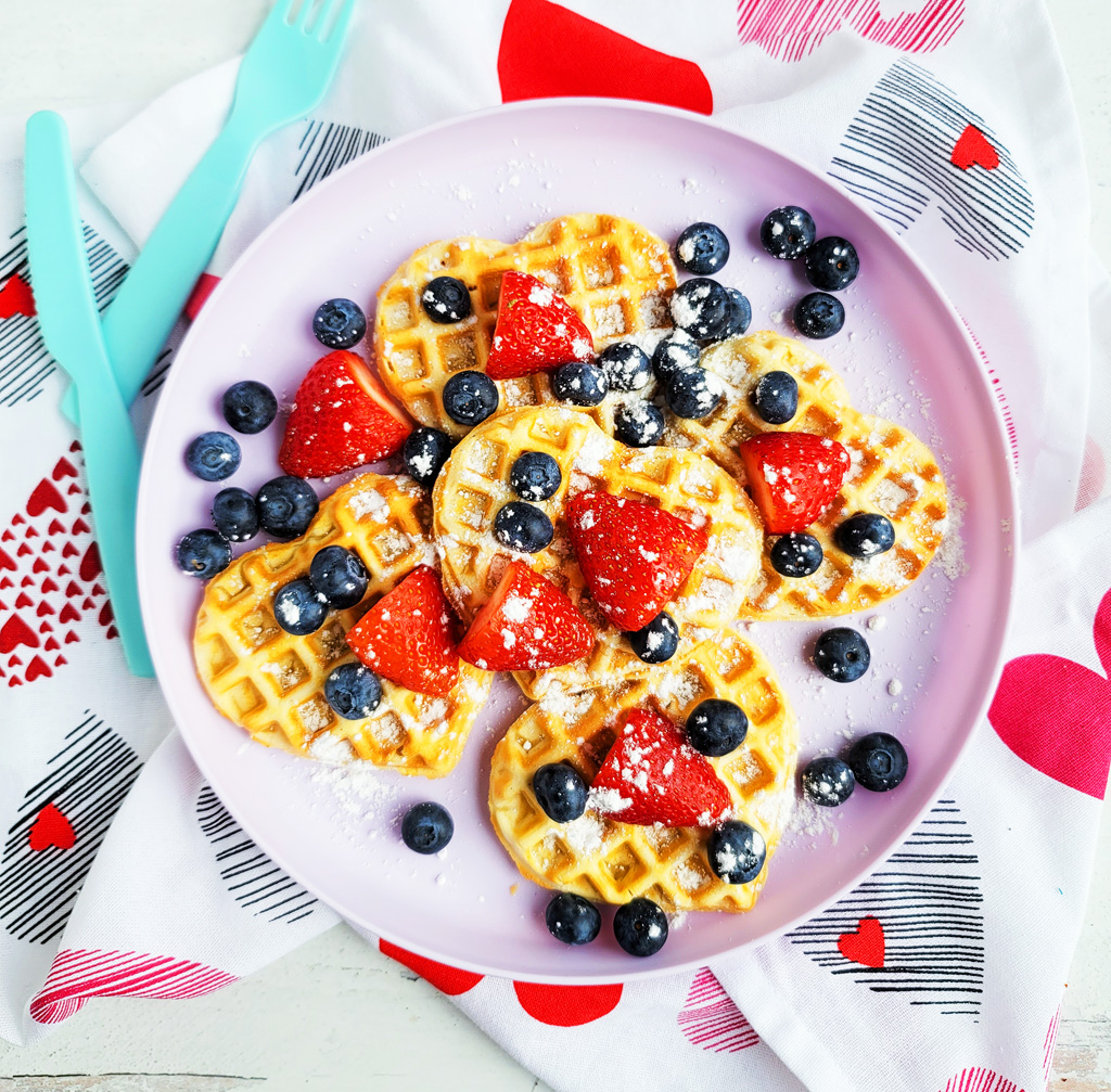 These Berry Yummy Mini Heart Waffles make the perfect Valentine's Day breakfast! So light and airy… and topped with delicious blueberries and strawberries. littleeatsandthings.com