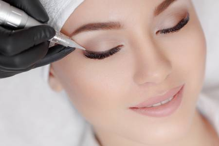 69336551-cosmetologist-making-permanent-make-up-at-beauty-salon