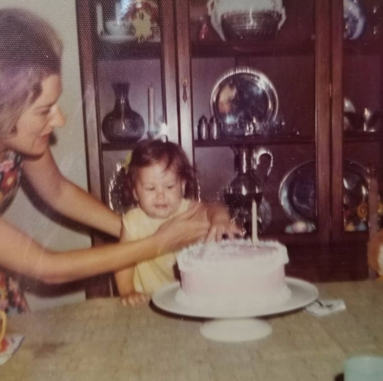 A one-year-old Beth Wagner watches her mom light the candle on her homemade cake.