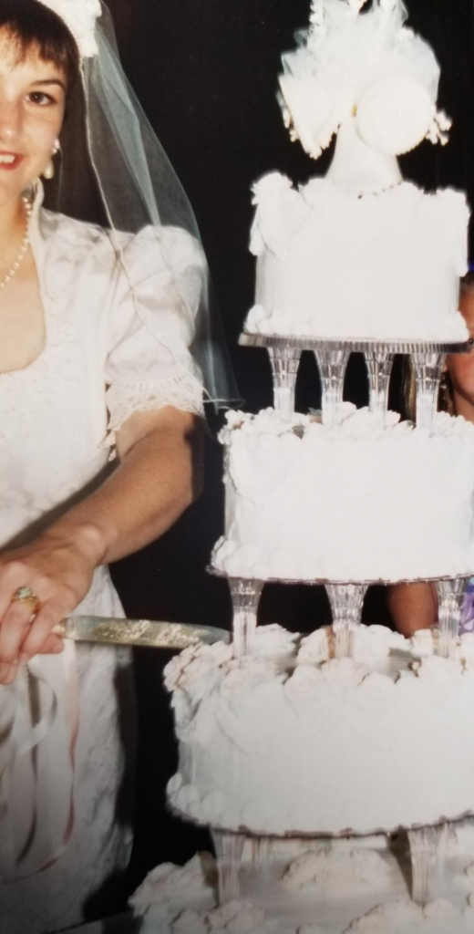 Beth Wagner on her wedding day with the cake her mom made.
