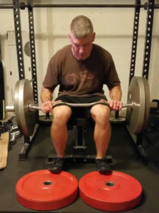 image shows how to perform the seated calf raise at home