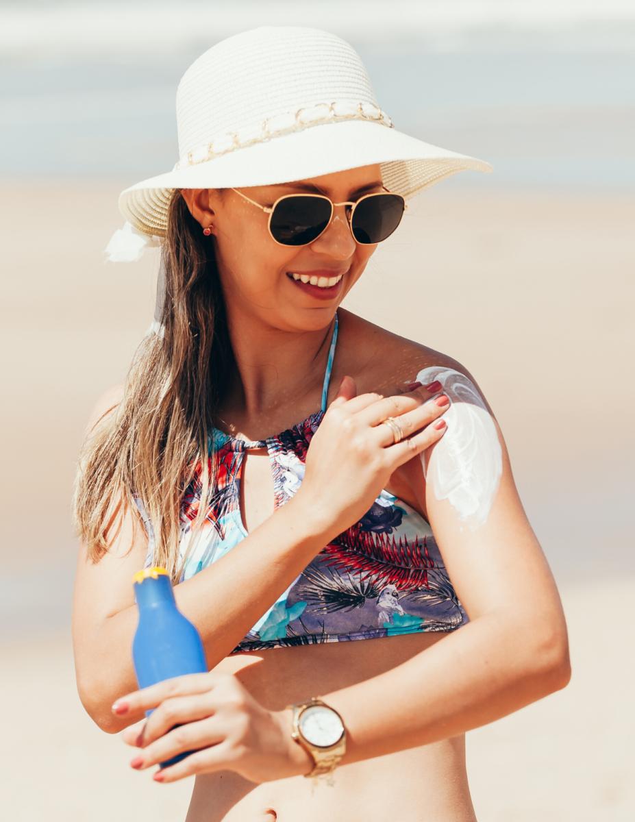 Woman at the beach applying sunscreen