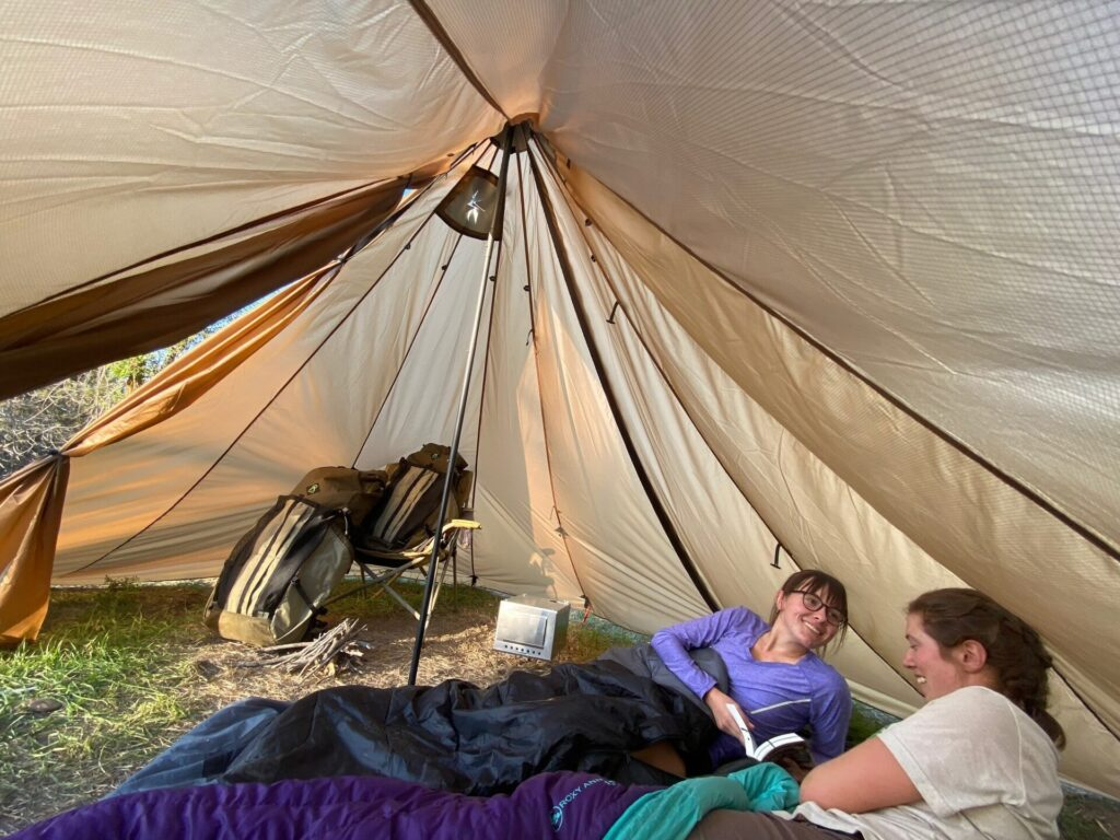 photo of two women inside the Redcliff tent with backpacks behind them.