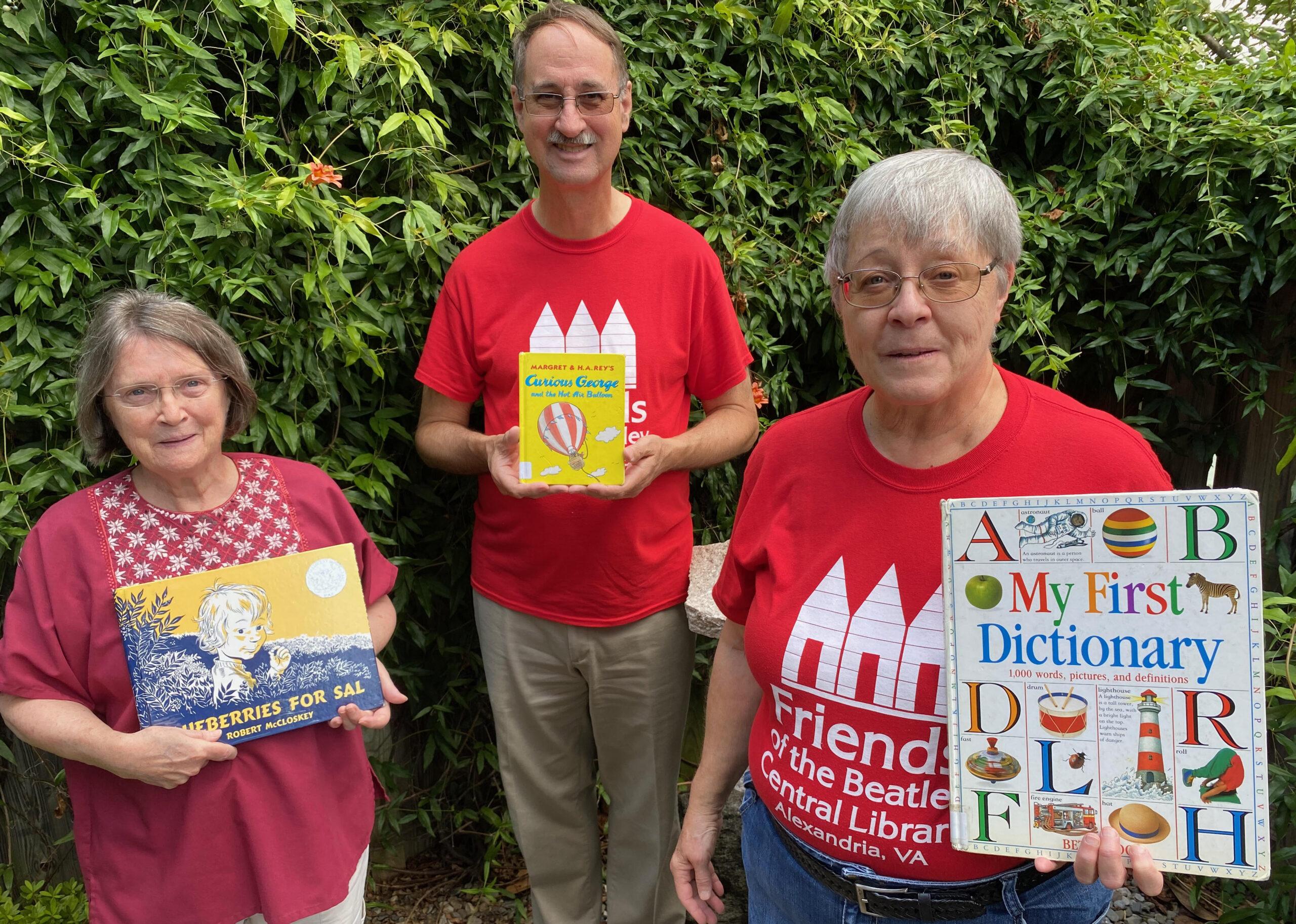 volunteers holding children's books