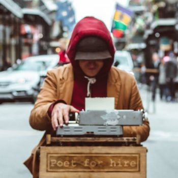 Man sitting at a typewriter outside on the street