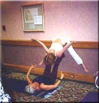 A deep stretch for the base chakra, demonstrated by Angela Farmer and student