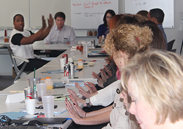 Marshawn teaches hand stretches to human resource managers at Baker Tilly accounting firm.