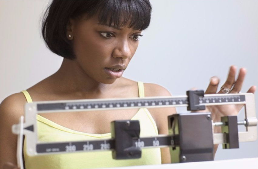 a women weighing her self on a scale with a worried face