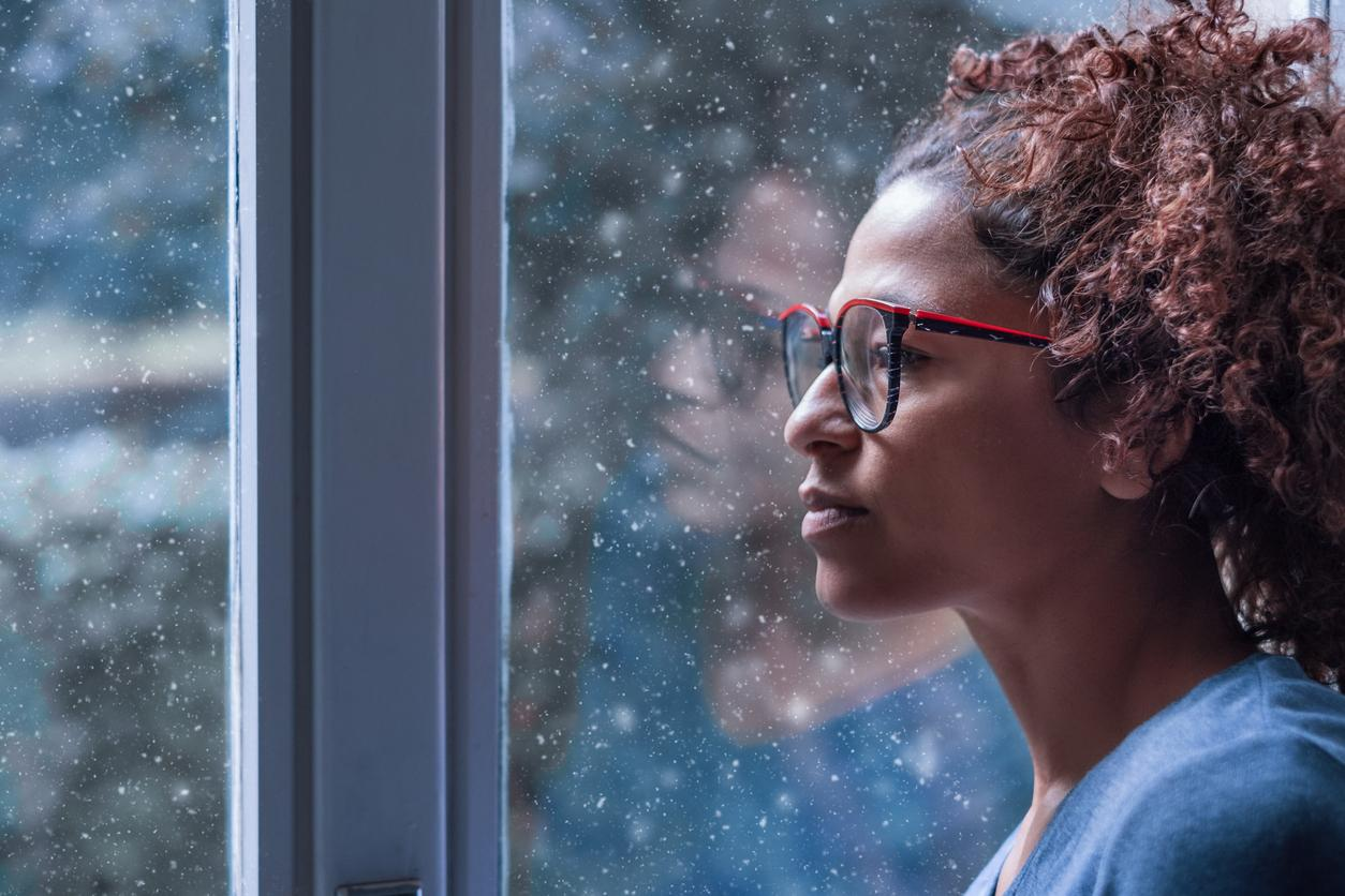 a women with glasses looking out a window at snow