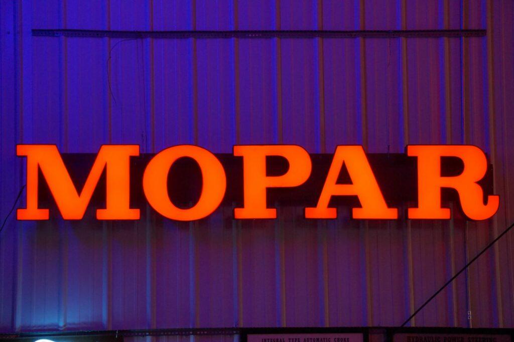 Lighted horizontal red Mopar sign.