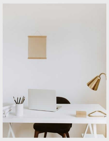a light grey laptop on a white office desk, a golden coloured desk lamp and a black seat in front of a white wall
