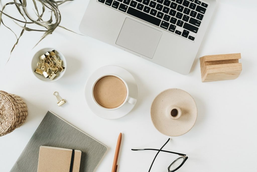 flatly image of a laptop, a cup of coffee, glasses and various items on a white office desk