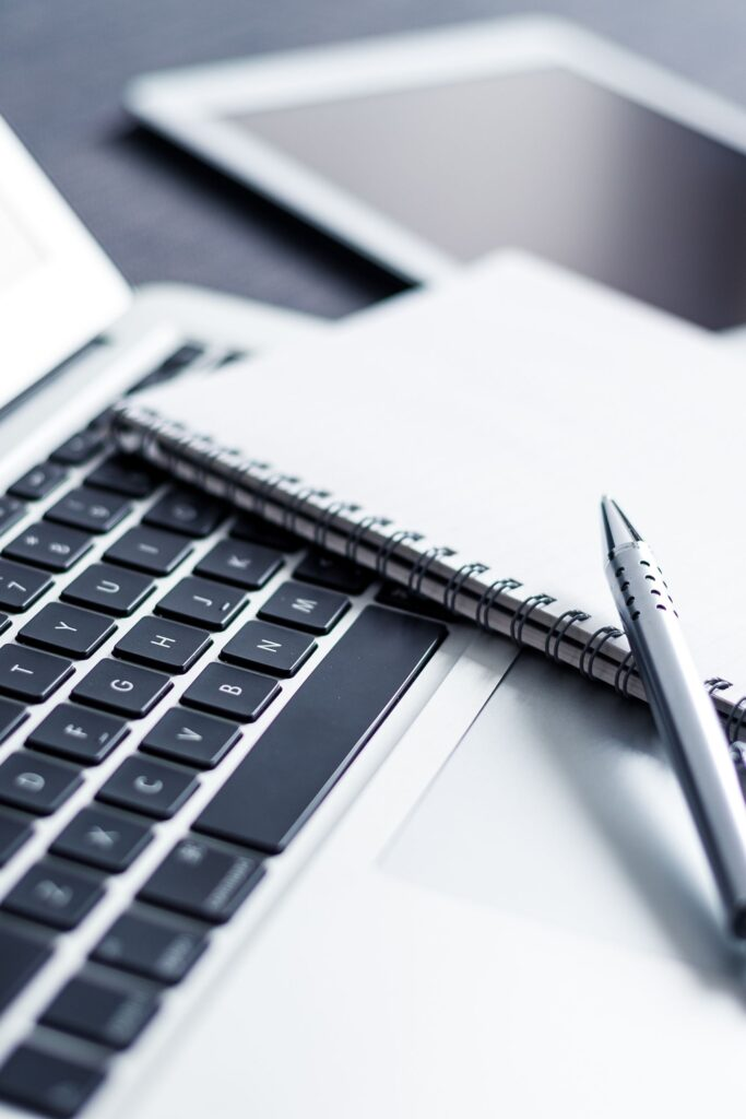a grey pen and a notebook on a laptop keyboard