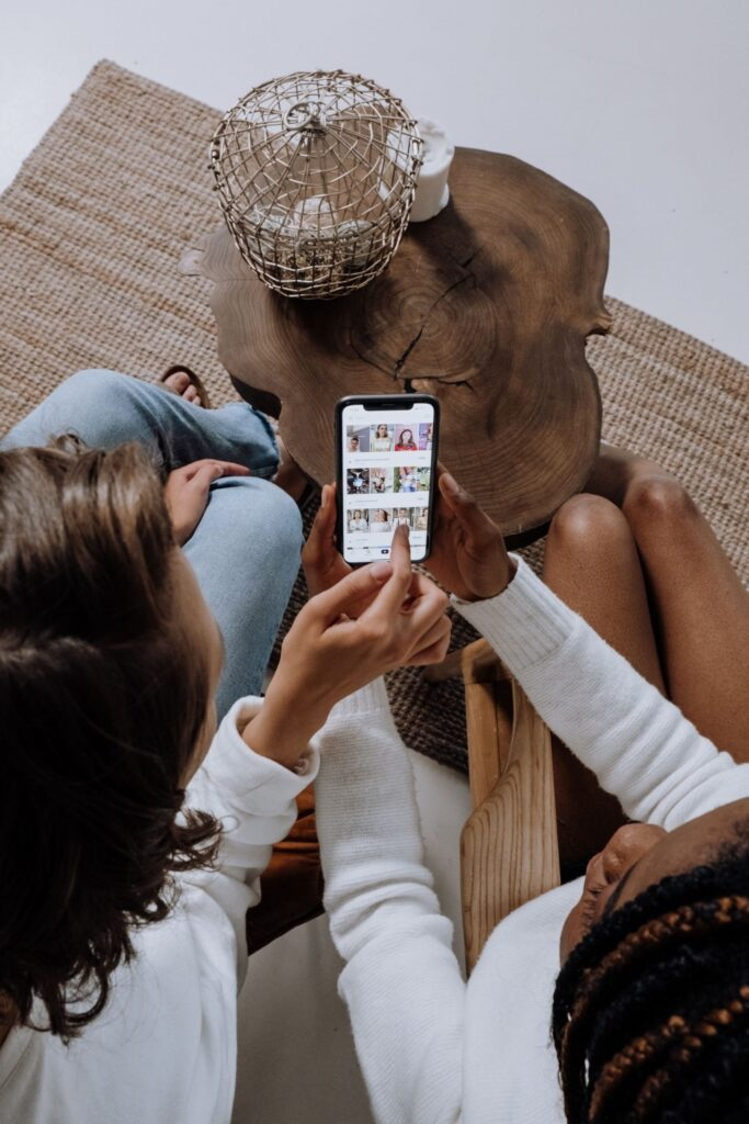 two girls wearing white tops are looking at a social media profile on a smartphone