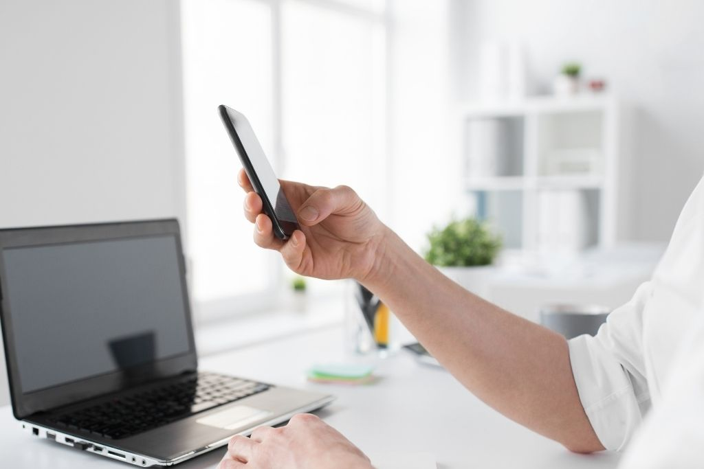 a black laptop and a hand holding a mobile phone in an office