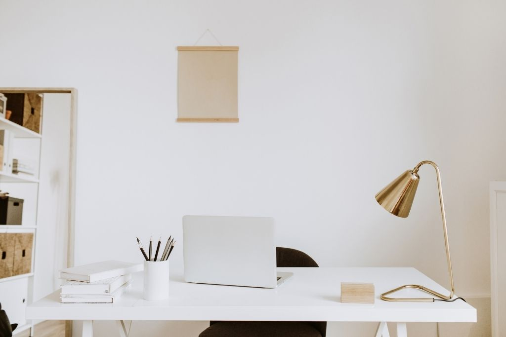 a grey laptop, a golden office lamp and a black chair in front of a white wall