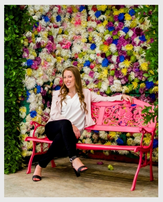 haley dagan sitting on a pink bench in front of a wall covered with colourful flowers