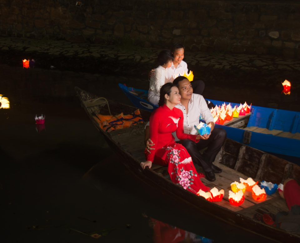 Couples go around in boats holding lights in Hoi An