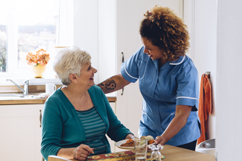aide assisting senior woman