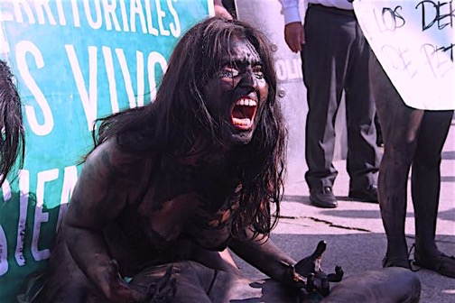 Protests: A woman painted in black screams as dozens of activists gather in front of Petroperu HQ