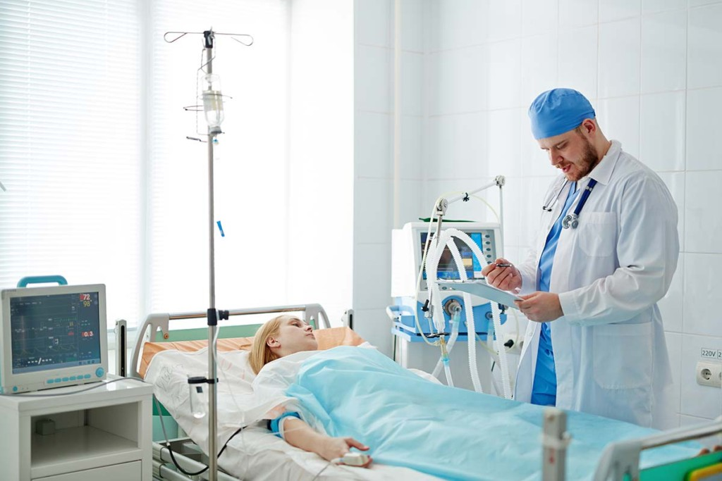 Doctor Standing At Bed With Patient Inside Mobile Intensive Care Facilities