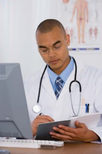 Doctor Writing In Notebook