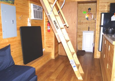 New River Tiny House hotel ladder to loft of tiny house with queen bed
