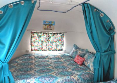 Airstream located at New River Gorge Campground looking to back at queen bed 2 twins on sides