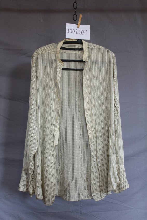 A white collared shirt on a hanger. Black vertical lines go down the front, while horizontal lines go across the cuffs.