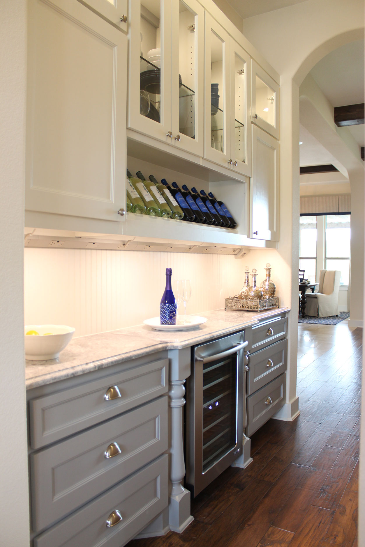 Burrows Cabinets' butler's pantry with Terrazzo door style in custom white and grey paint with half round posts, wine storage, glass panel doors, sweep blocks