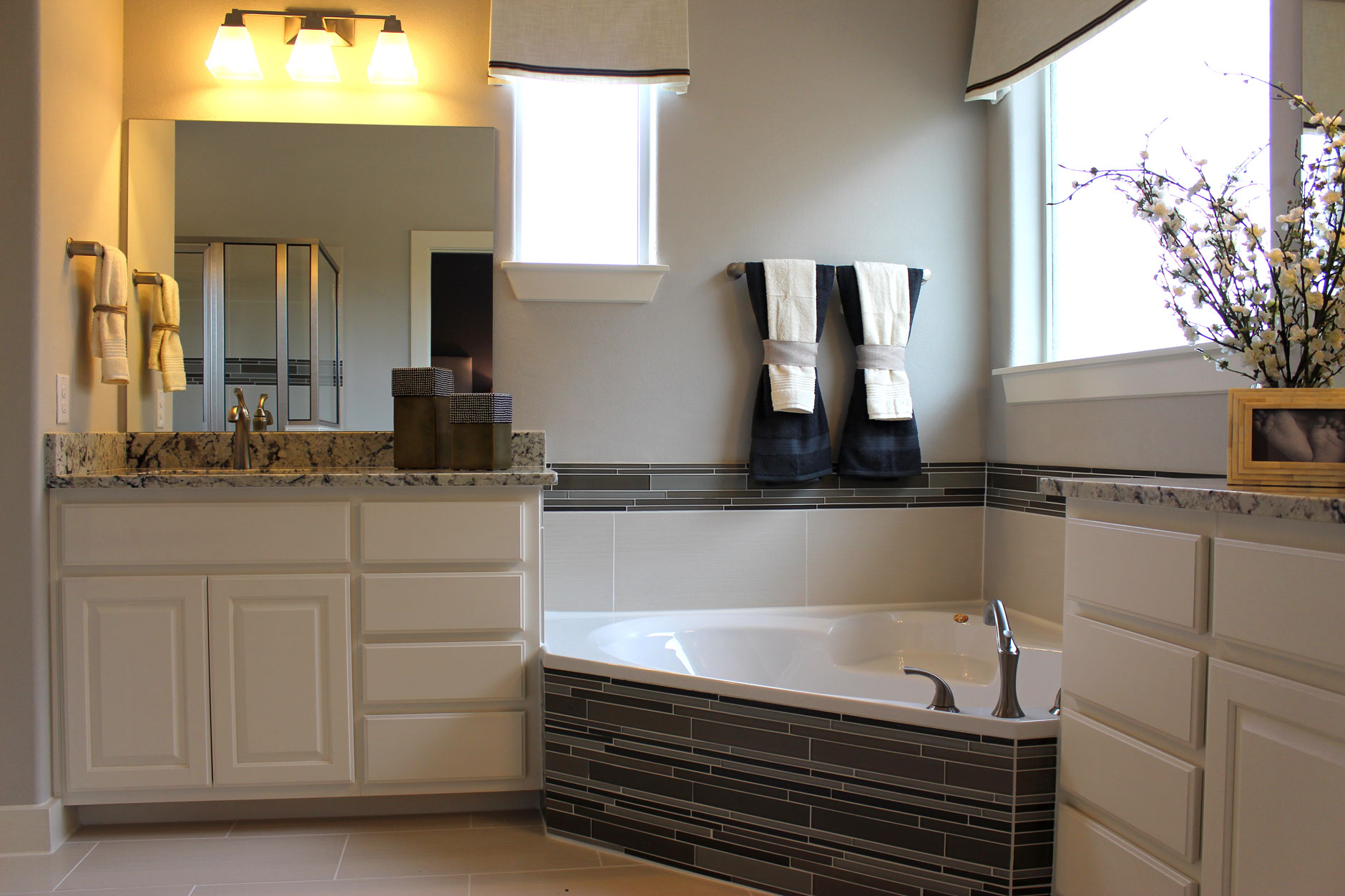 White master Bath cabinets by Burrows Cabinets with corner tub