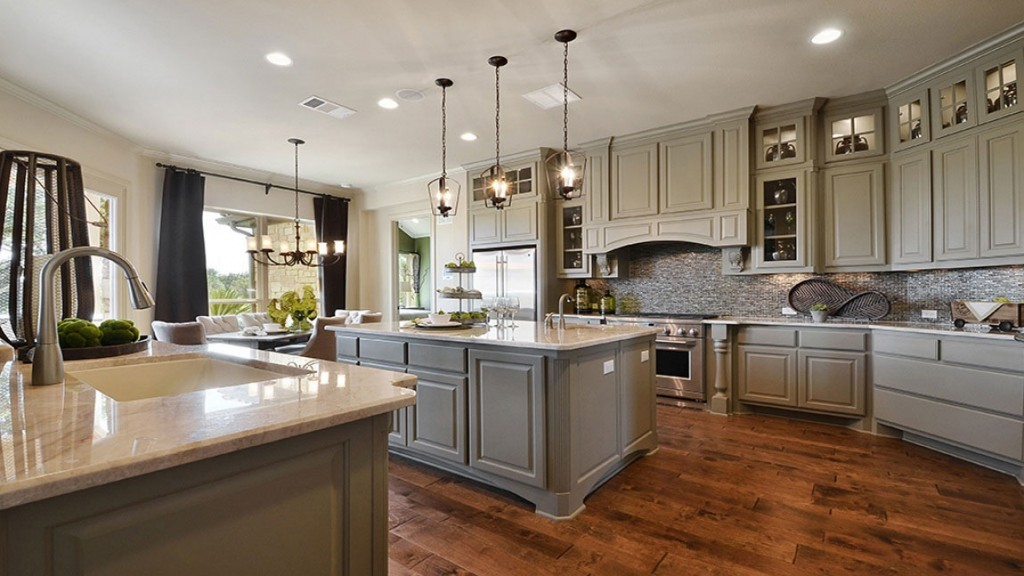 Burrows Cabinets kitchen with Elite vent hood integrated island corners and Monaco posts in Ecru
