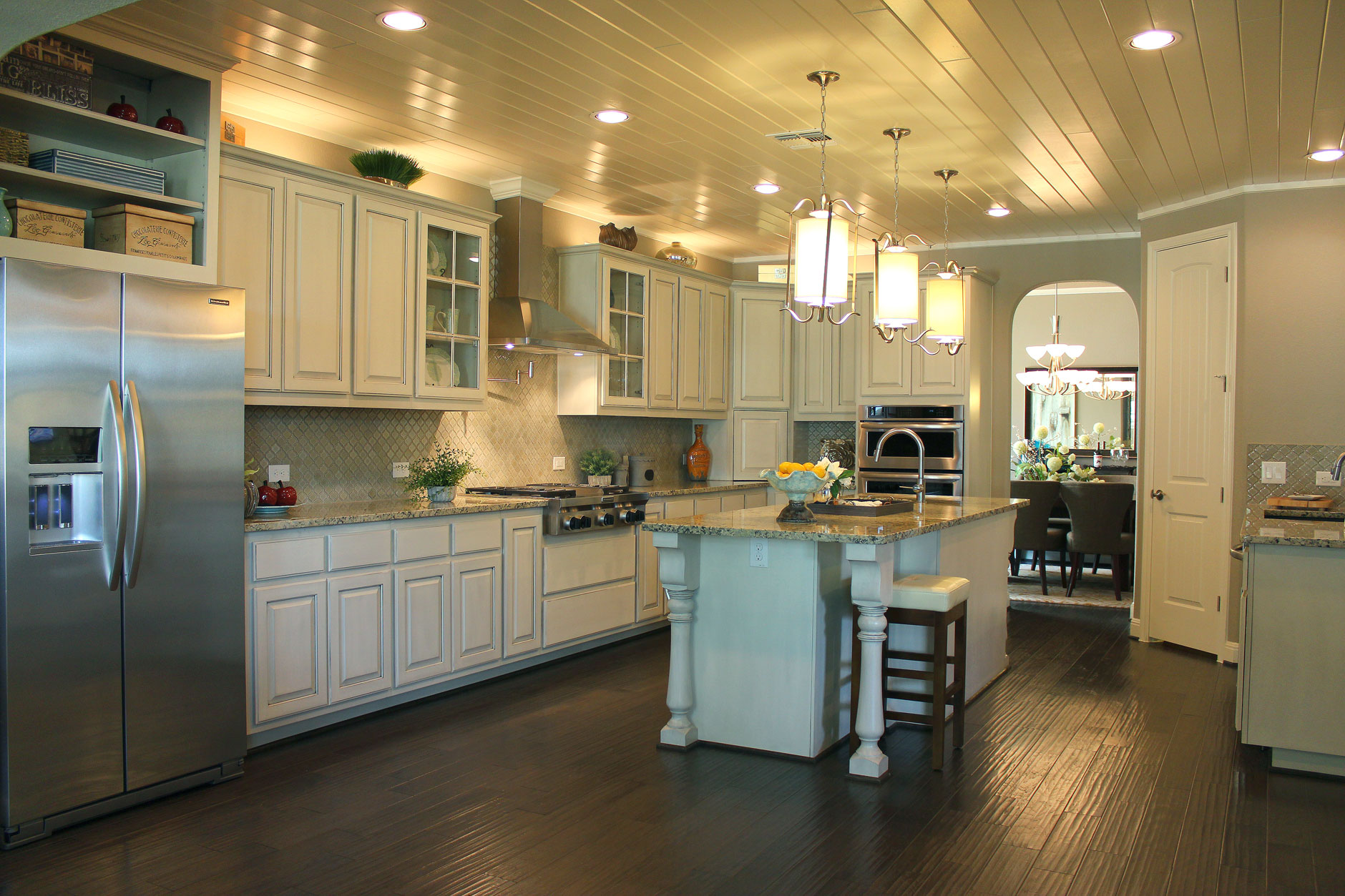 kitchen with island posts and open shelves above refrigerator in bone with black glaze