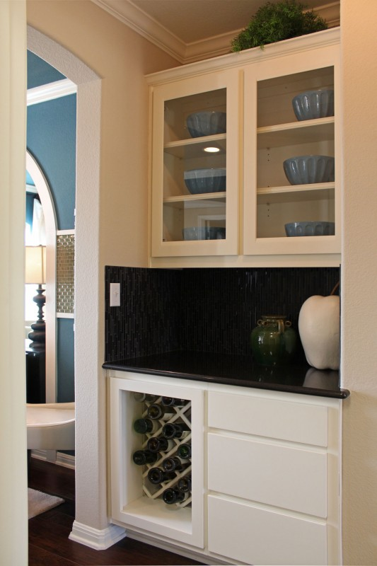 Burrows Cabinets' butlers' pantry with white cabinets in Briscoe design in Bone, glass panel doors and lattice wine rack