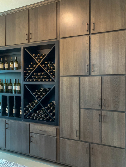 Burrows Cabinets' dining room cabinet wall with modern slab soco door in hickory driftwood