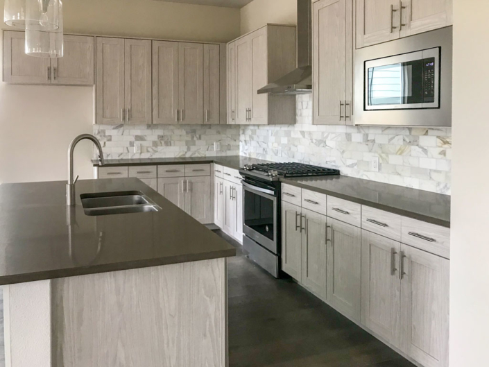 Kitchen EVRGRN Artisk 5pc with gray and white backsplash