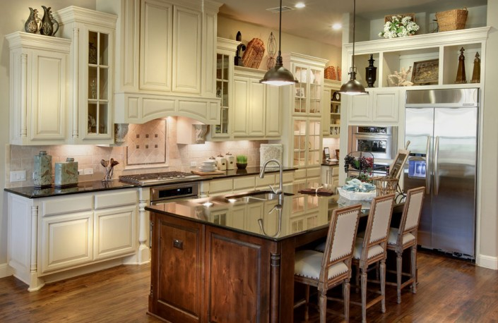Burrows Cabinets' kitchen in bone with brown glaze including Elite vent hood, and knotty alder island