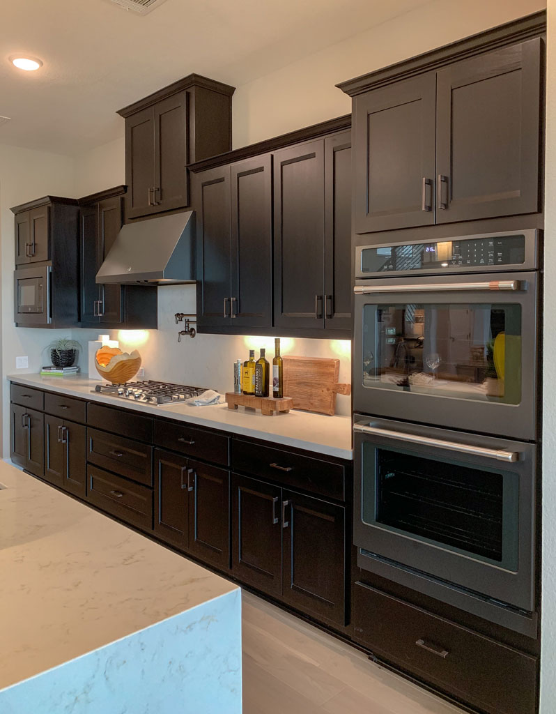 Kitchen wall cabinets in Beech Espresso by Burrows Cabinets with Briscoe doors and slate black appliances