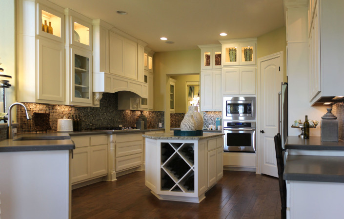 Burrows Cabinets kitchen cabinets with Briscoe door style in Bone, big x wine rack and Elite vent hood