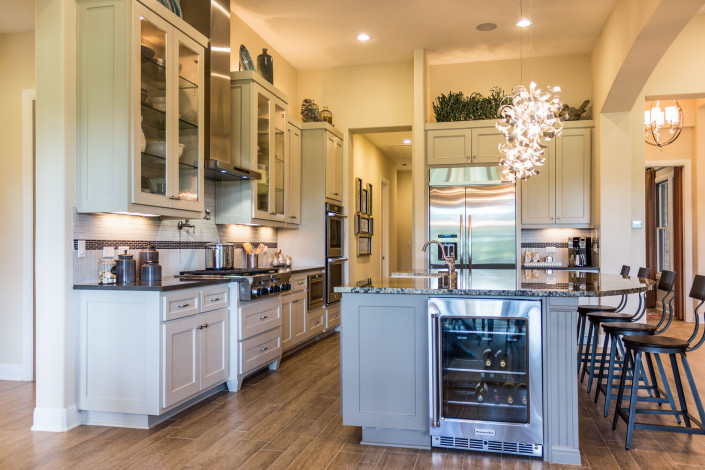 Burrows Cabinets' kitchen with wood floors and beaded shaker-style Kensington doors in white with gray island