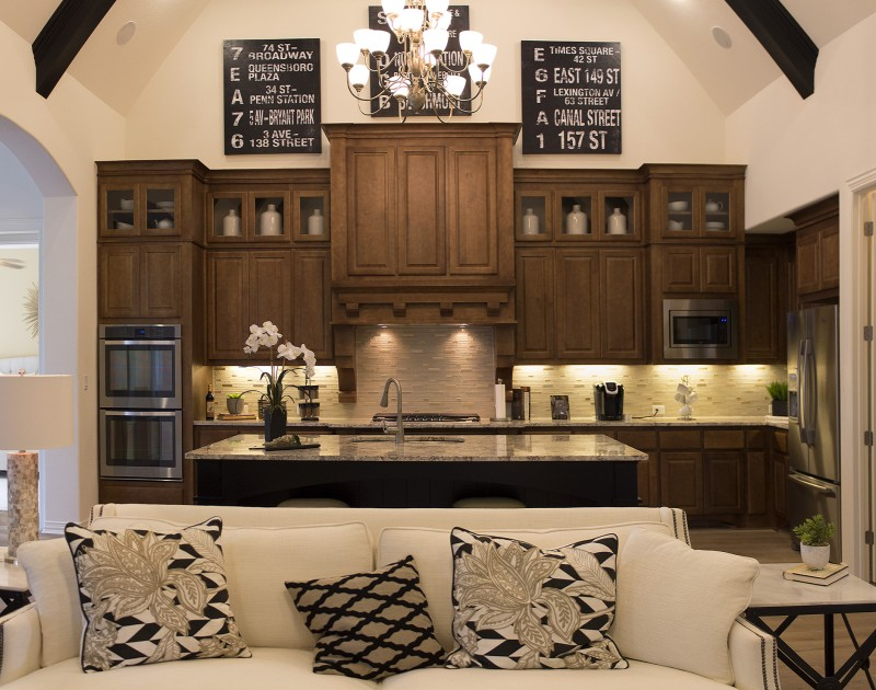 Burrows Cabinets' kitchen cabinets with raised panel doors custom Maple stain, glass inserts in uppers and custom wood vent hood