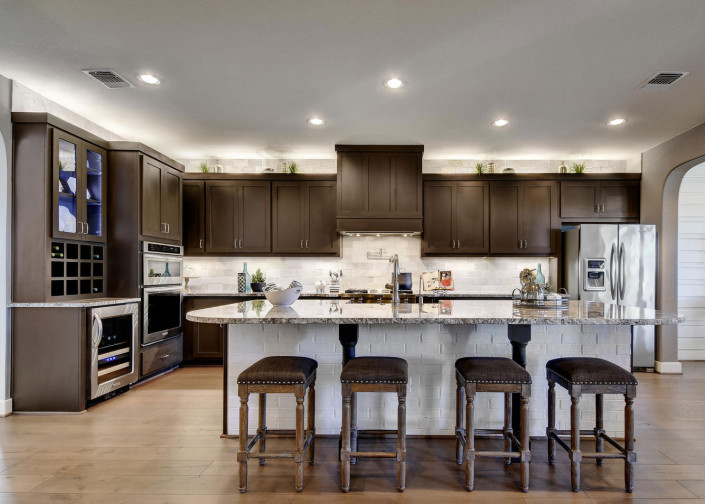 Burrows Cabinets' kitchen with shaker doors, custom vent hood and bottle storage in Bistre
