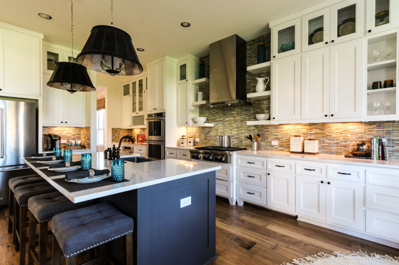 Burrows Cabinets' white kitchen with gray island and Terrazzo doors