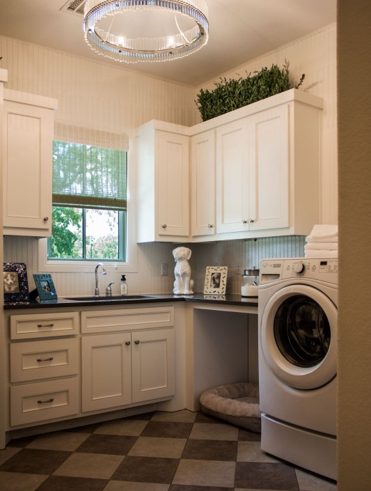 Burrows Cabinets' laundry room cabinets with Kensington doors and dog bed open space
