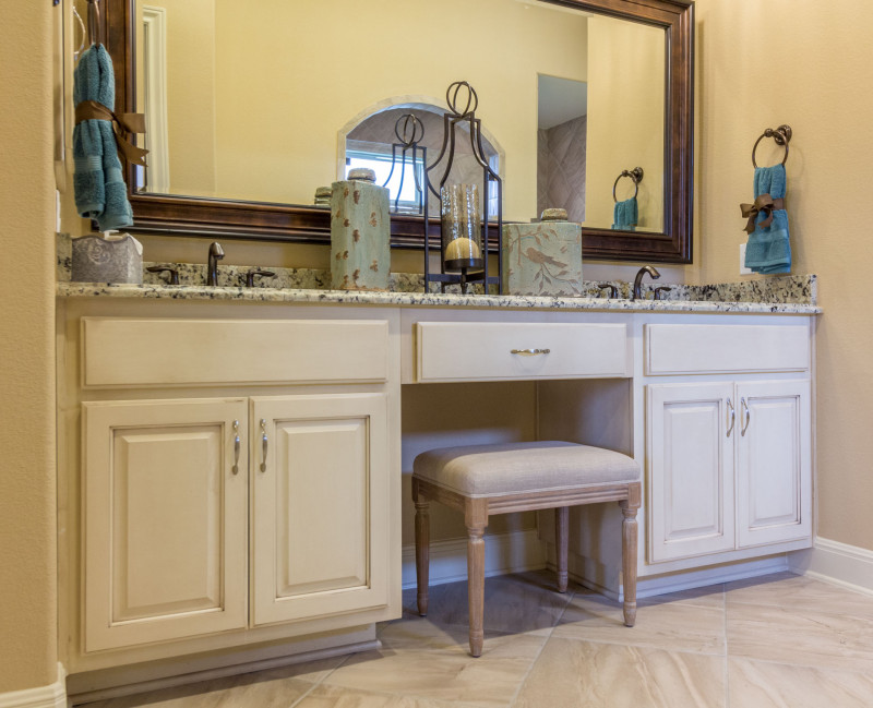 """Burrows Cabinets' master bath cabinets in bone with brown glaze and """"knee space"""" sitting vanity"""