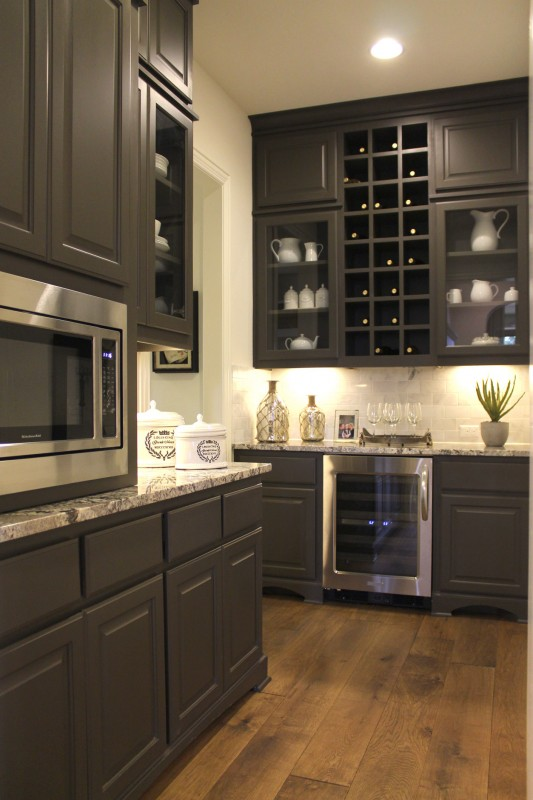 Burrows Cabinets' pantry cabinets with wine storage and glass doors in Umber gray