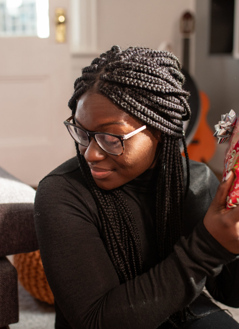 A Black woman is holding a picture of a Christmas gift.